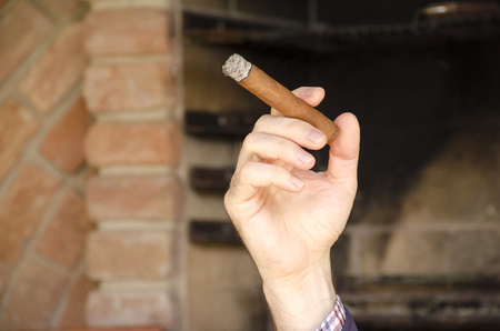 A man hand holds a cuban cigar front of  a blurred brick wall and fireplace in background. Reklamní fotografie