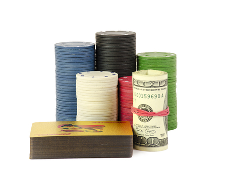 A stack of chips stay on whitte background with roll of dollars and gold cards.