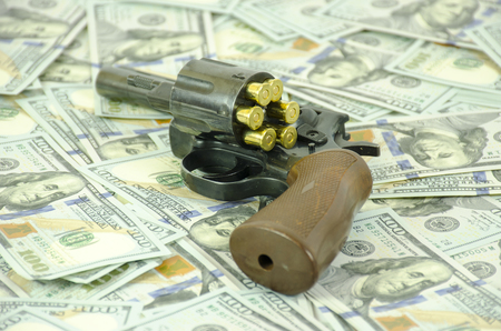 A weapon with load bullets laid down on blurred dollars.