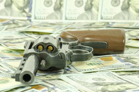 Une arme avec des balles de charge posées sur des dollars flous.
