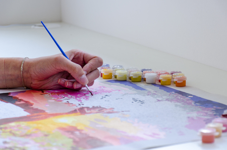 Hand of young woman is painting by brush a picture on the table.
