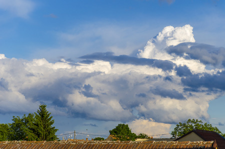 A big cloud above roofs before started storm with blue sky in background.