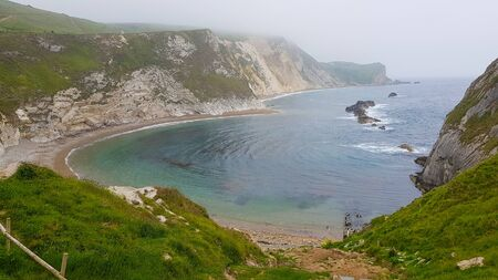 The bay with rock Durdle Door under fog and cold weather. Banco de Imagens