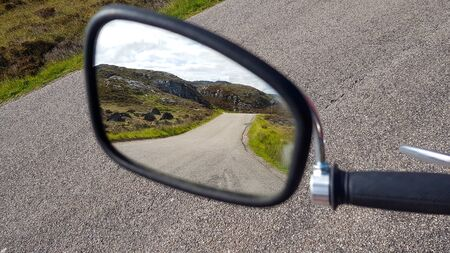 A view to blurred old motorbike mirror with a road in reflextion somewhere in Scotland.