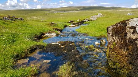 A view to English landscape with brook stones under blue sky with clouds. Banco de Imagens