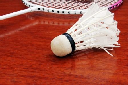 battledore: Badminton Racket and Shuttlecock on wooden floor.