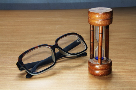 Eyeglasses and hourglass on the desk  photo