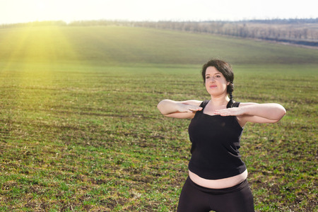 overweight woman doing exercises in countryside in the meadow Stock Photo