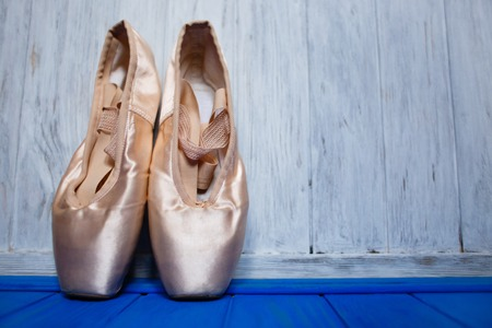 Ballet pointe shoes on bright color  wooden background, free  sp