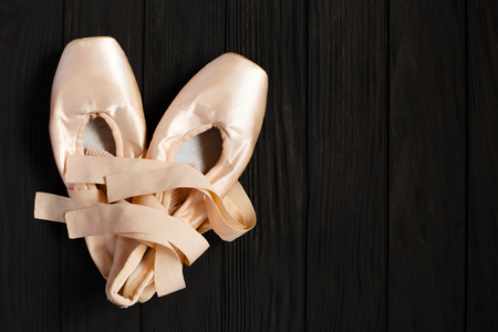 Ballet pointe shoes on black wooden background, free space Stock Photo