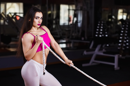 Young attractive muscular sexy fitness woman pulling rope in gym