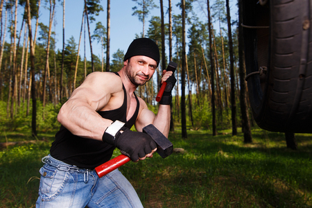 Strong healthy adult ripped man with big muscles hitting car tyr Stock Photo