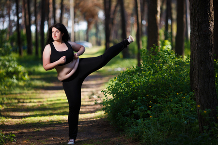 Young overweight woman working out in the park Stock Photo