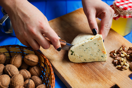 Woman hands cutting spicy homemade cheese on cutting board, serv Stock Photo