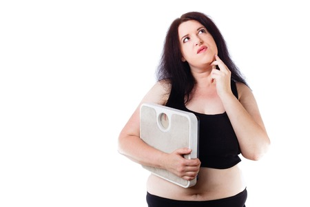 Young overweight thoughtful woman holding scale in hand Stock Photo