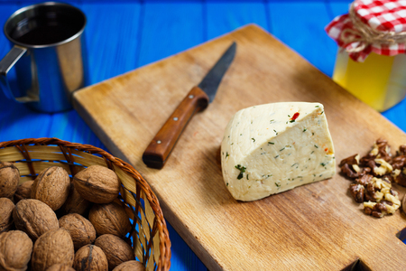 Piece of homemade spicy cheese with walnuts,mug of homemade wine