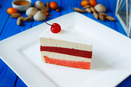 Mousse cherry cake sliced on white squared plate close-up served