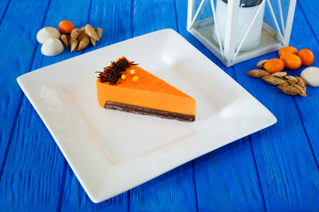 Traditional autumn sweets. Mousse pumpkin cake tart sliced on sq Stock Photo