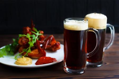 Beer snacks, pub, kitchen background, restaurant menu. Two mugs Stock Photo
