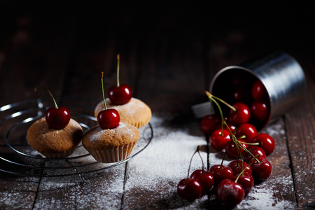 Delicious cakes and sprinkled cherries on rustic wooden table. K