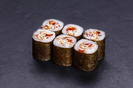 Traditional sushi rolls with smoked eel, unagi sauce and sesame