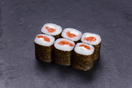 Classical Japanese cuisine, sushi rolls with salmon on black sto