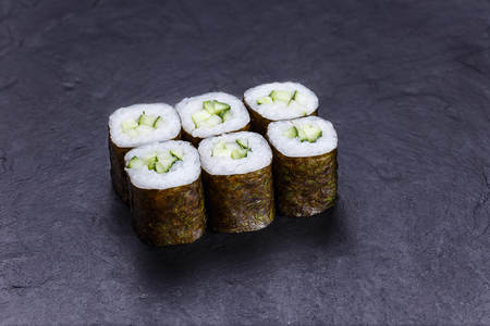 Sushi rolls with cucumber, served on black stone slate. Japanese