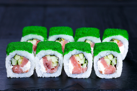 Sushi roll with pink salmon, decorated with caviar Stock Photo