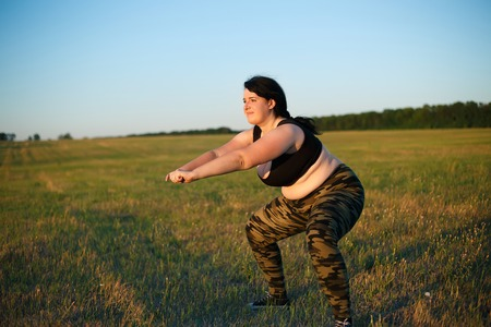 Overweight fat woman squats in the meadow on the grass. Weight l