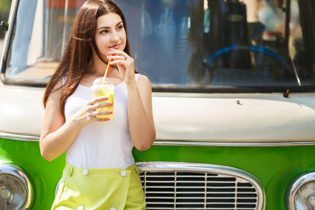 Young pretty woman drinking lemonade on vintage car background