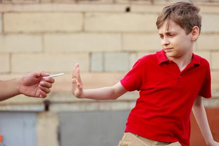 Schoolboy refuse the proposed cigarette. Bad habits, healthcare,