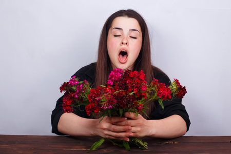 Sneezing young woman holding bouquet of flowers. Allergy, medici