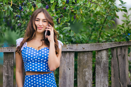 Woman talking on smart phone outdoors. Cropped image of young pr