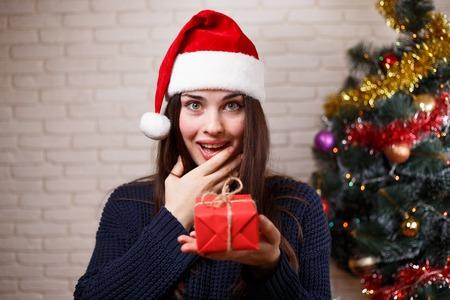 Young cute surprised woman in Santa cap is surprised to get a pr Banco de Imagens