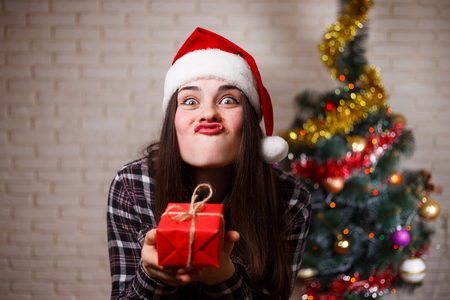 Portrait of funny grimacing cute joyful woman in Santa cap with
