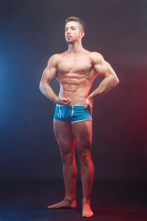 Young handsome muscular man bodybuilder with perfect abs, should