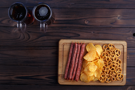 Dark beer and beer snacks set. Top view on table with two mugs o