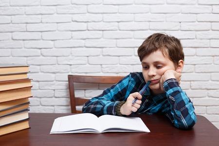 Elementary school kid biting a pen pondering over the task solut