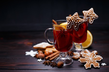 Christmas mulled wine and gingerbread cookies on dark wooden tab