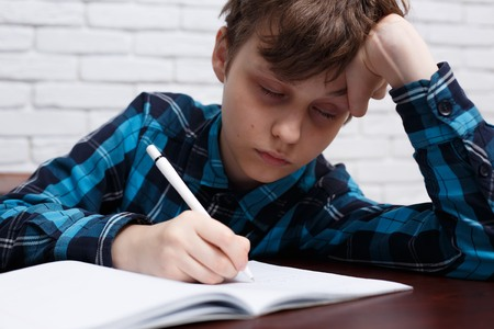 Tired schoolboy falling asleep while studying at copybook. Study Standard-Bild