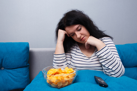 Fat overweight woman with chips while watching TV. Sedentary lif