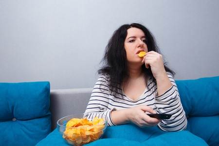 Fat overweight woman sitting on the sofa, eating chips while wat