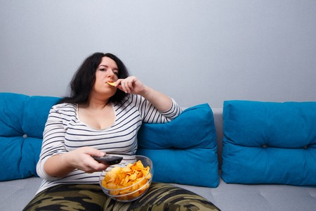 Couch potato overweight woman sitting on the sofa, eating chips Foto de archivo