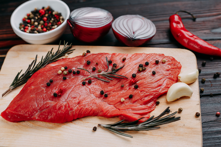 Raw meat, beef steak with rosemary, garlic and spices close up o