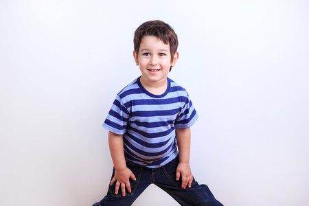 Little lovely boy smiling and posing, studio shoot on white. Emo