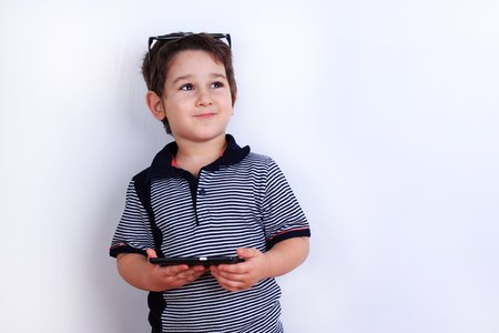Dreamy smiling cute boy with smartphone in hands. Technology, mo