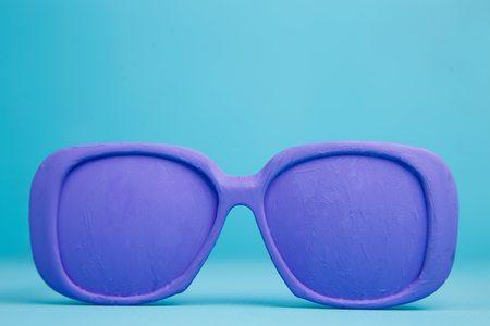 Fioletowe jasne pastelowe okulary na niebieskim tle, wakacje, spr