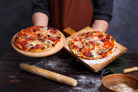 Chef baker in apron holding boards with hot freshly baked pizza