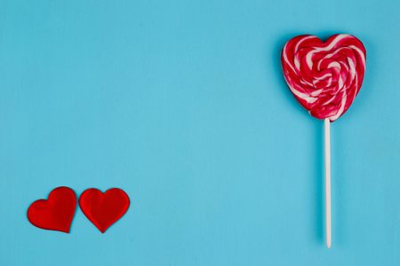 Two red fabric hearts and sweet bright lollipop heart on blue ba