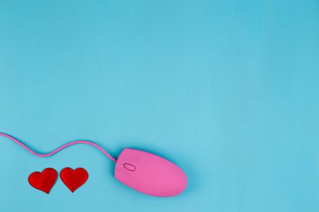 Love chat, online dating. Pink computer mouse with red fabric he Stockfoto